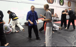 Colin Frye, in blue, works with a student at the Internal Energies and Takedowns workshop.